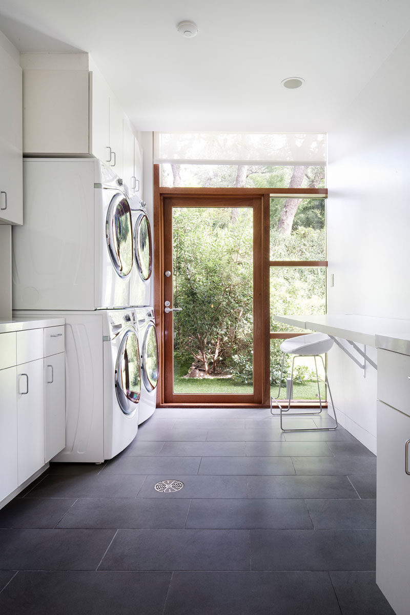 This large laundry room has double washing machines and dryers, as well as plenty of storage and folding space.