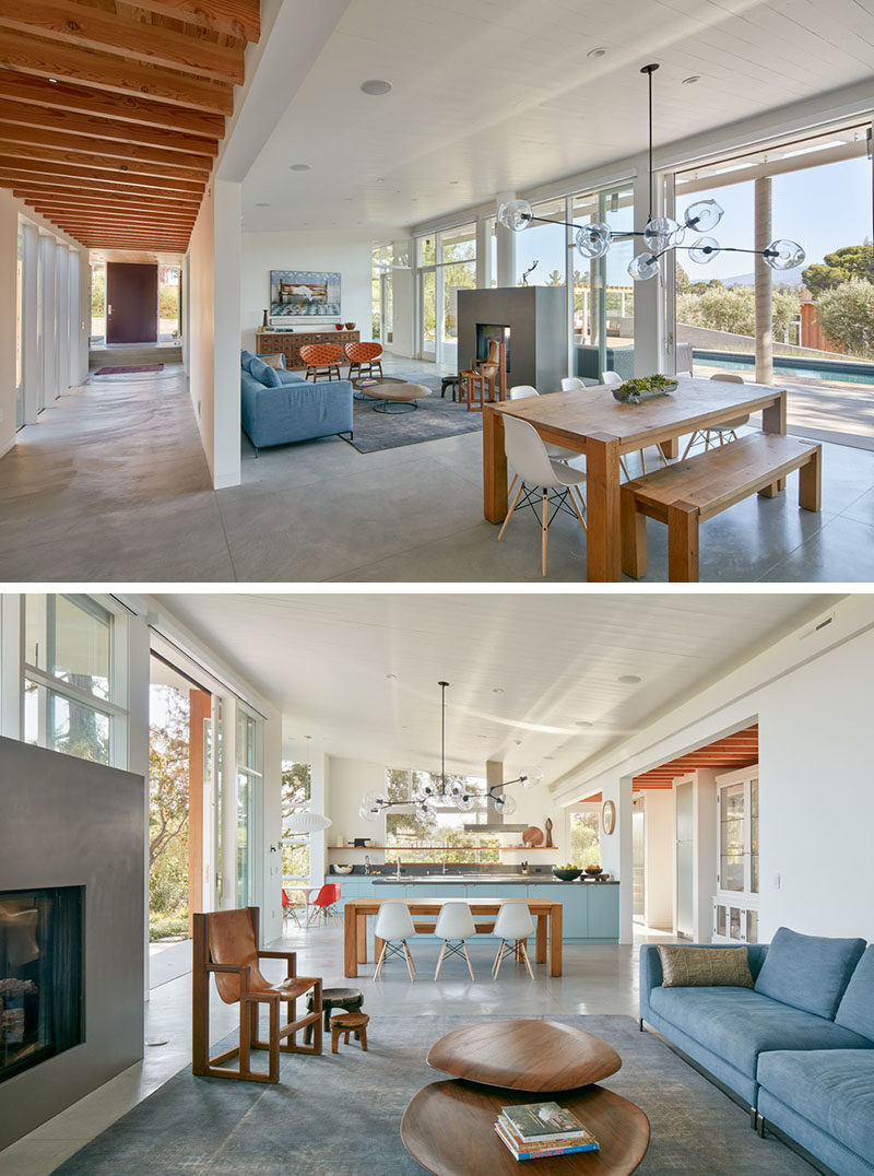 In this living area, there's a double-sided fireplace that can be enjoyed from the living room and the outdoor living space too. Between the living area and the kitchen is a large wooden dining table with a sculptural pendant light.