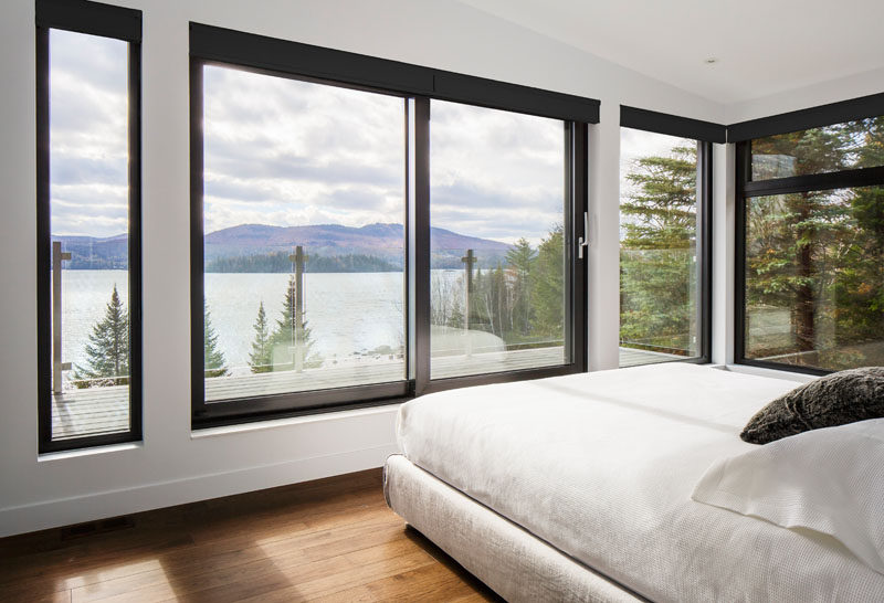 This master bedroom has black window frames that contrast the white walls, and a door leads to a private balcony with amazing lake and mountain views.