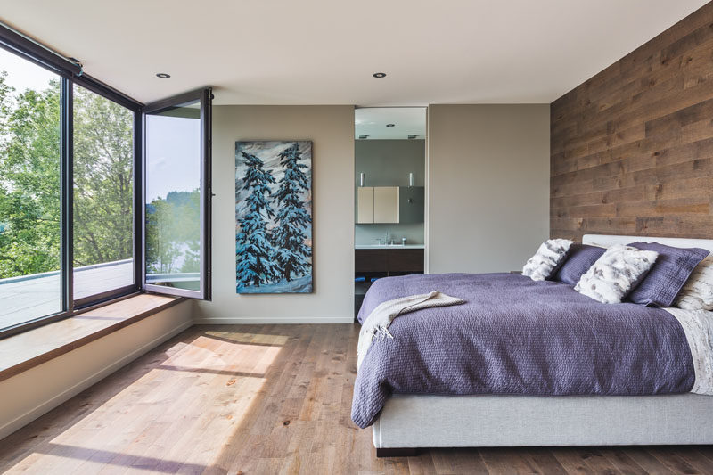 In this bedrooms there's a built-in window seat, a wooden accent wall that matches the floor, and an ensuite bathroom.