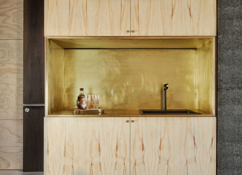This backyard retreat has plywood walls and a small kitchen with brass detailing.