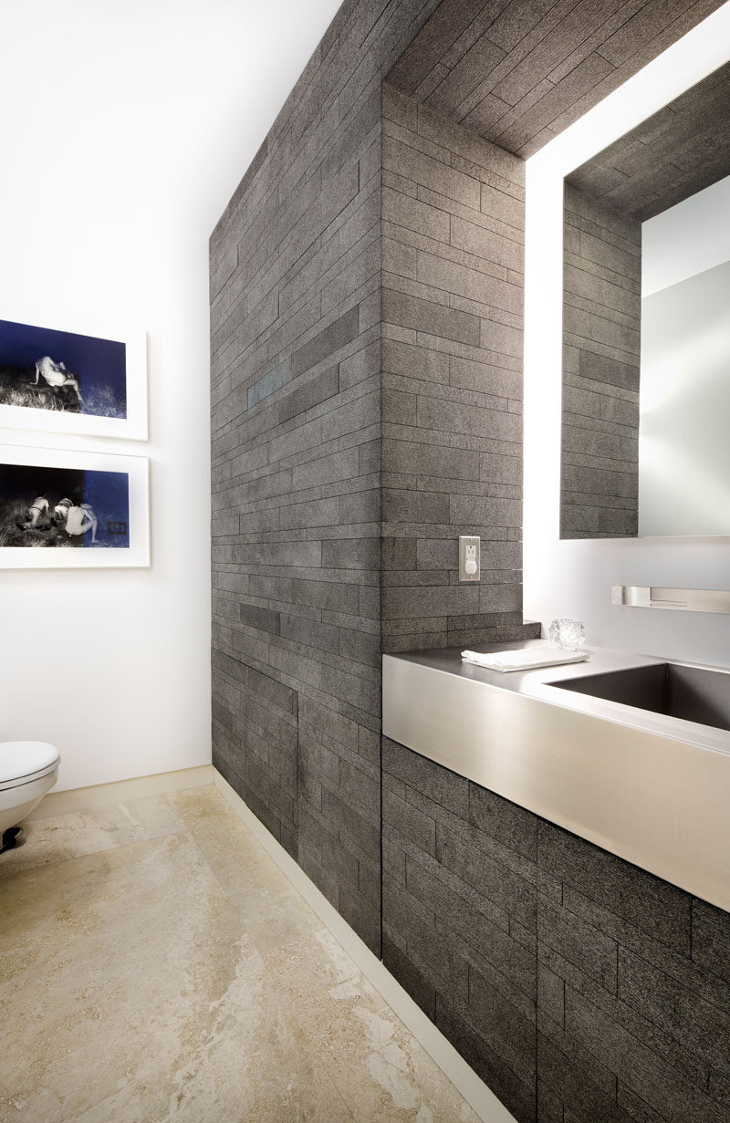 This bathroom has hidden cabinetry and lighting that surrounds the mirror.