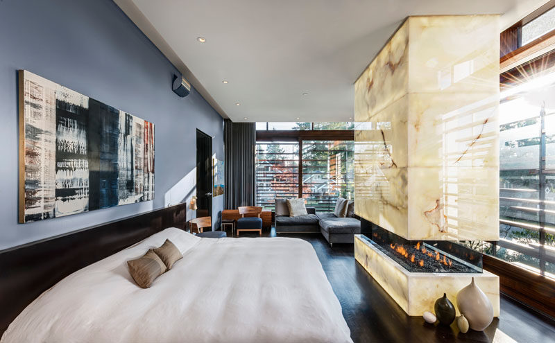 In this modern master suite there's a stone-covered fireplace at the end of the bed and a private lounge area off to the side.