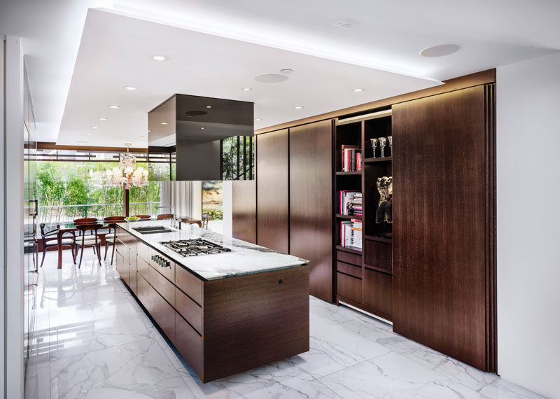 In this kitchen, white marble surfaces have been combined with dark wood cabinetry to create a warm modern appearance.