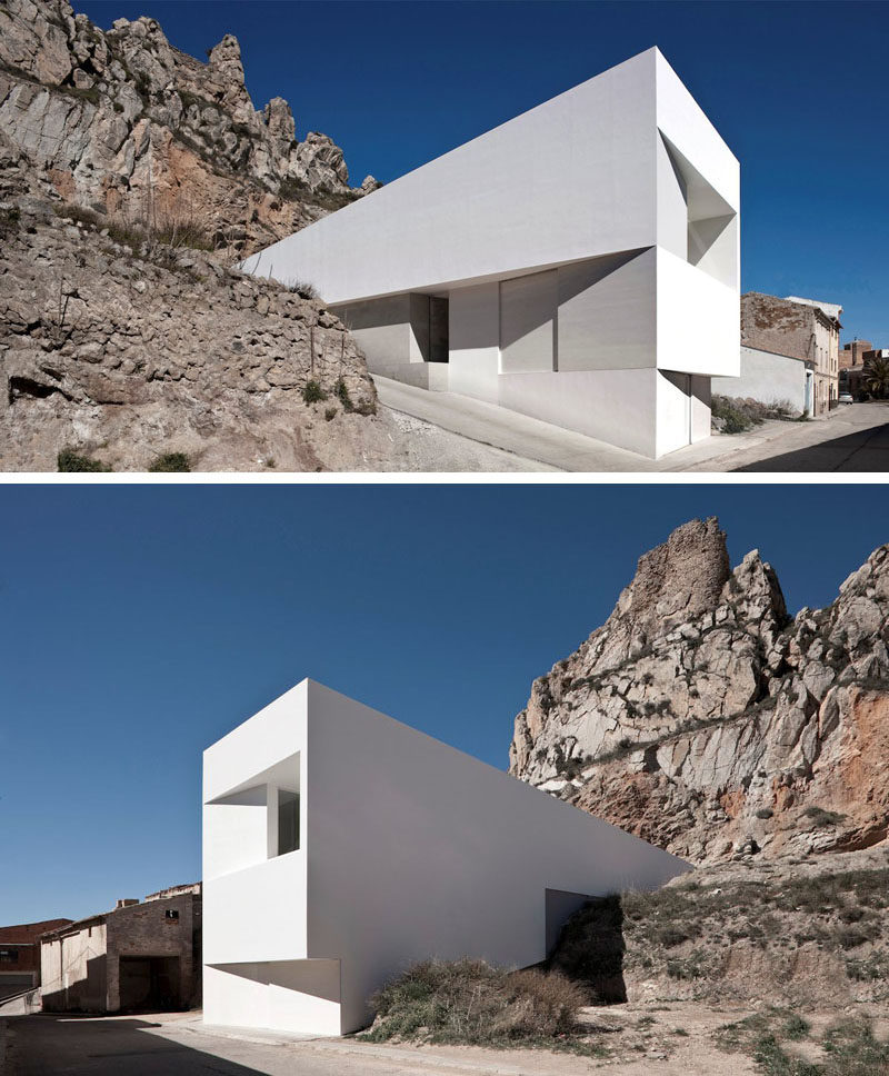 House Exterior Colors - 11 Modern White Houses From Around The World // This large, white, rectangular house appears to be emerging right out of the rocks from the mountain behind it.