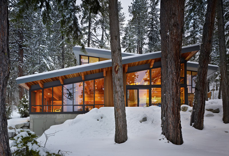 16 Examples Of Modern Houses With A Sloped Roof | This modern lake house has multiple sloped roofs to allow the rain and snow to easily slide off.