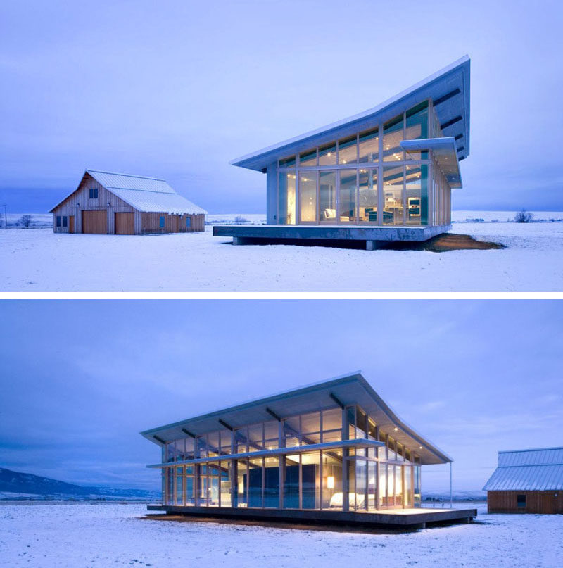 16 Examples Of Modern Houses With A Sloped Roof | The sloped roof on this modern glass farmhouse mimics the look of half of the barn behind it.
