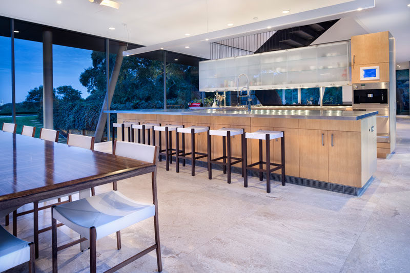 This kitchen with a long island separates the dining area from the stairs and living room.