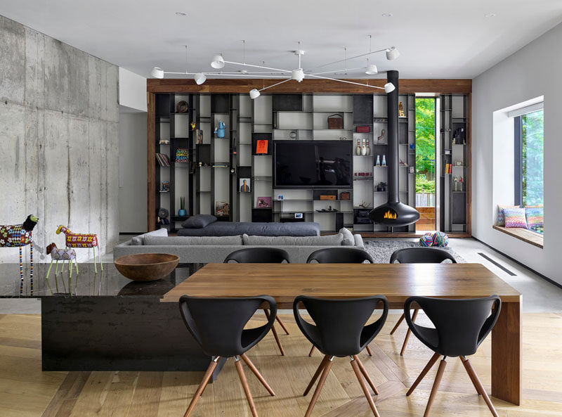 A Long Dining Table Divides The Open Floor Plan On One End Is The Family Room With A Custom Designed Metal Bookcase And A Suspended Black Wood Burning