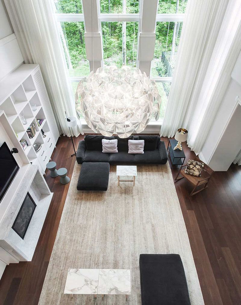 The dark wood floors of this living room are brightened up by the tall windows and large light colored rug
