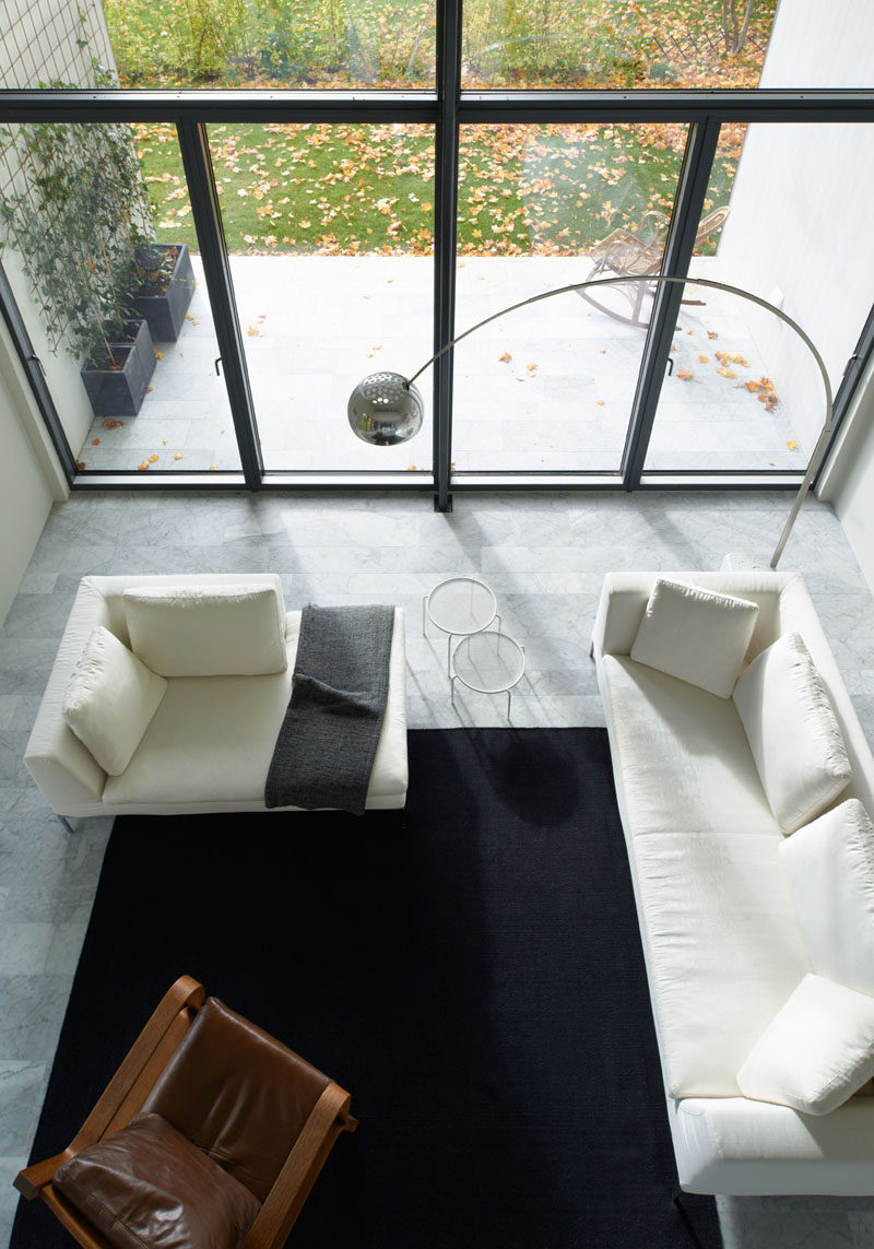 Interior Design Ideas - 17 Modern Living Rooms As Seen From Above | White couches, a leather chair, and a large dark area rug give this living room a bright and open look that also feels cozy and warm.