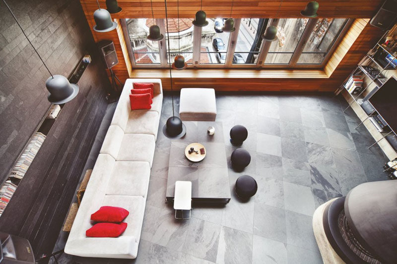 Interior Design Ideas - 17 Modern Living Rooms As Seen From Above | The stone tiles along the back wall of this living room combined with the wood feature wall and stone tiles give this loft an industrial yet warm feel.