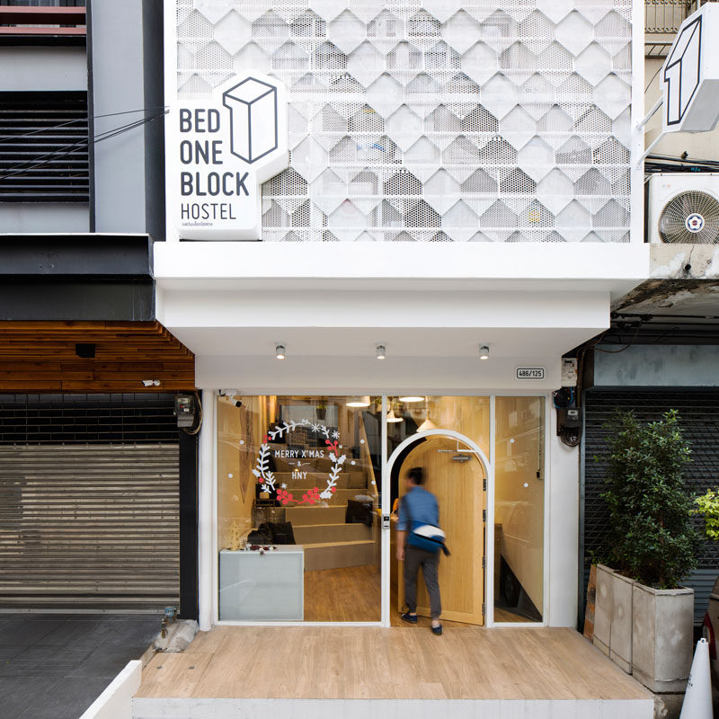 This modern hostel in Bangkok has a welcoming entrance with a wood door surrounded by windows letting you see inside, which is a strong contrast to the surrounding buildings with their metal doors and bars.