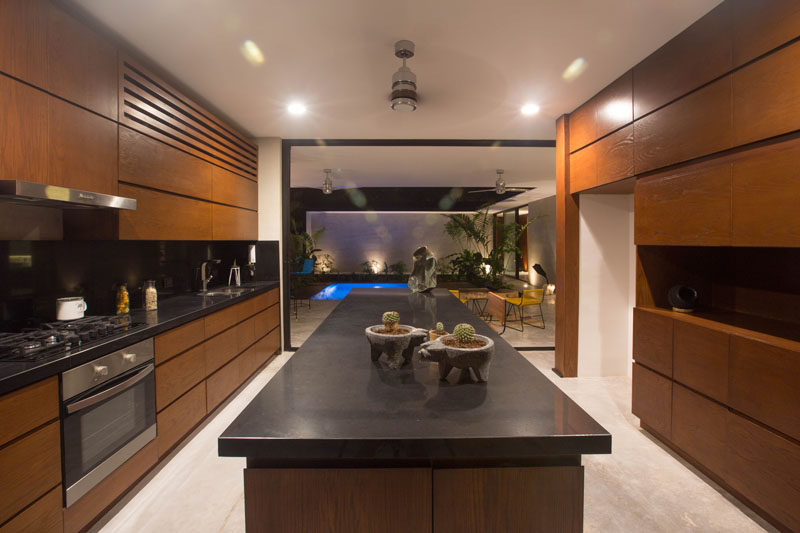 This mostly wood kitchen with black countertops opens up to a courtyard with small swimming pool.
