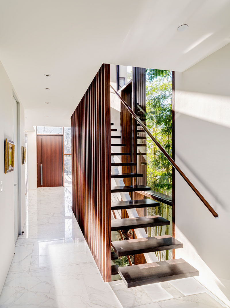 This modern wood staircase matches the wood used on the front door, and is a strong contrast against the white walls and white marble flooring.