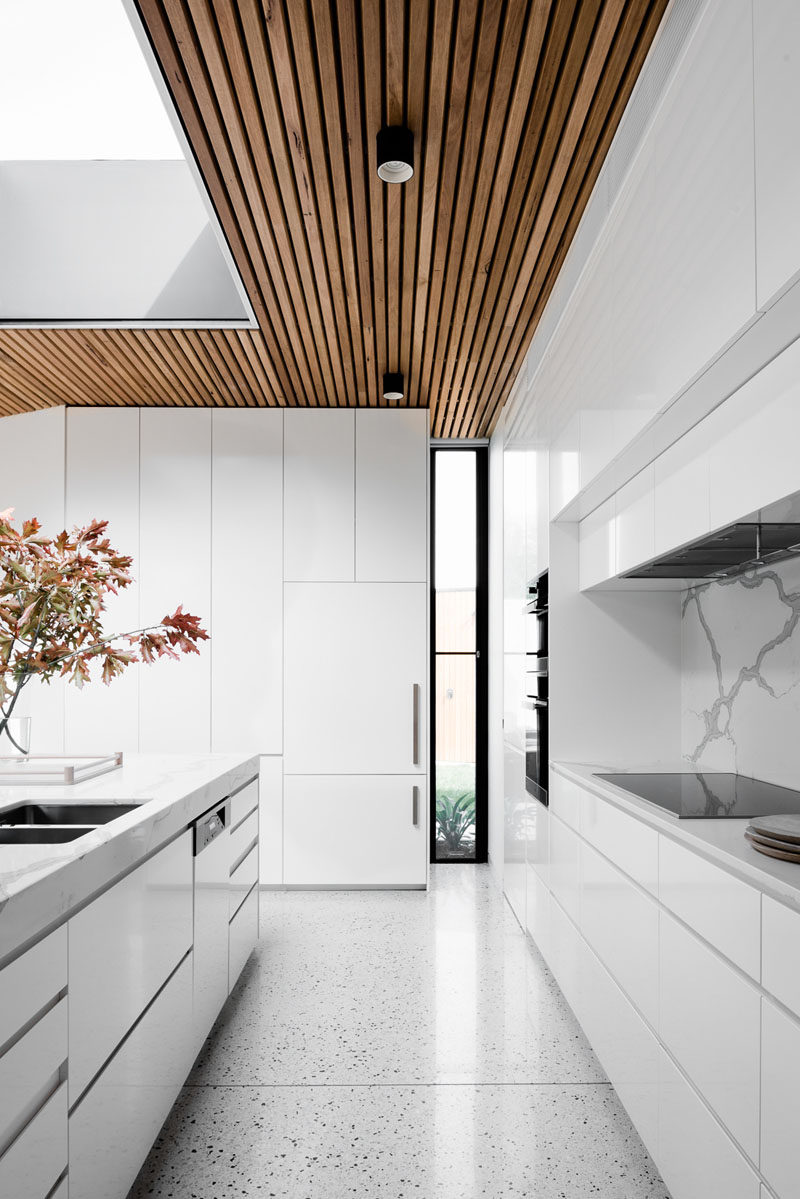 Window Style Ideas - Narrow Vertical Windows // This kitchen is already bright thanks to the all white interior but the narrow window in the corner brings in just an extra bit of light and adds some contrast with its black window frame.