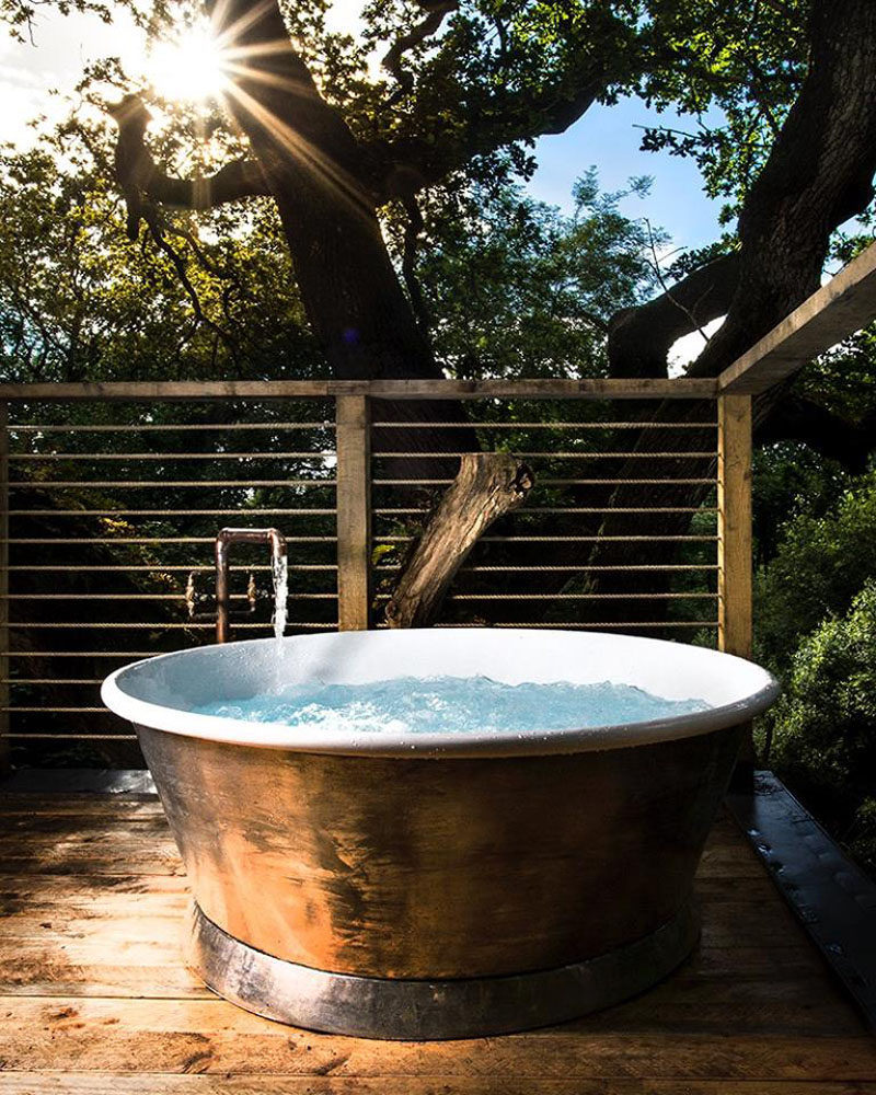 On the second storey of this grown-up treehouse, there's a large soaking tub on the rooftop deck.