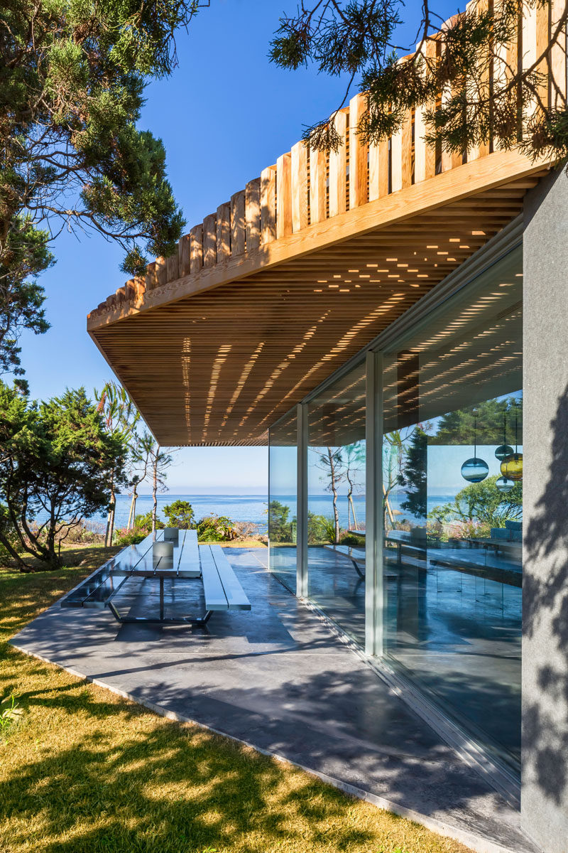Off to the side of the dining area and kitchen in this modern villa, is an outdoor dining area set up with a large picnic style table with benches.