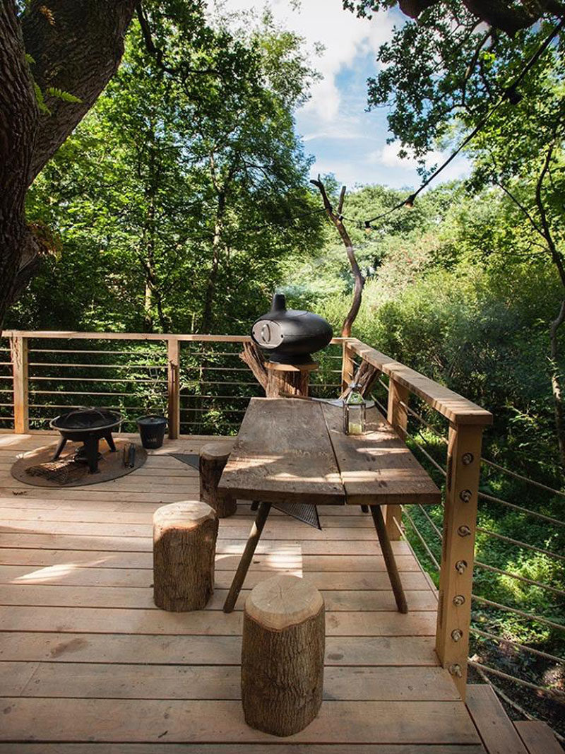 This modern treehouse has a bbq and dining area on the deck that wraps around a tree.