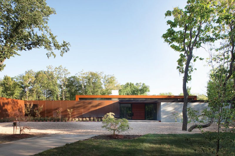 15 Single Story Modern Houses | The exterior of this single story house is clad in steel that creates harsh lines but that are softened by the trees surrounding it.