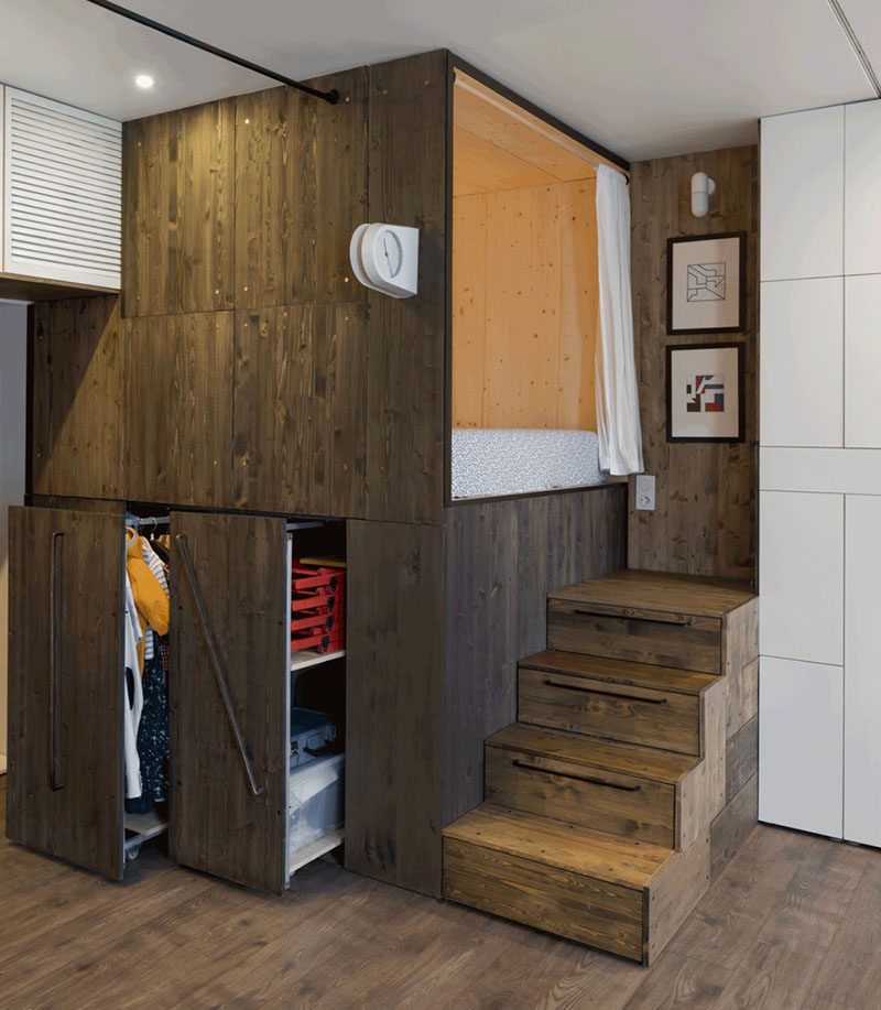 This small 376 sqft apartment has a raised bed to create additional closet space underneath, and the stairs leading to the bed have built-in storage.