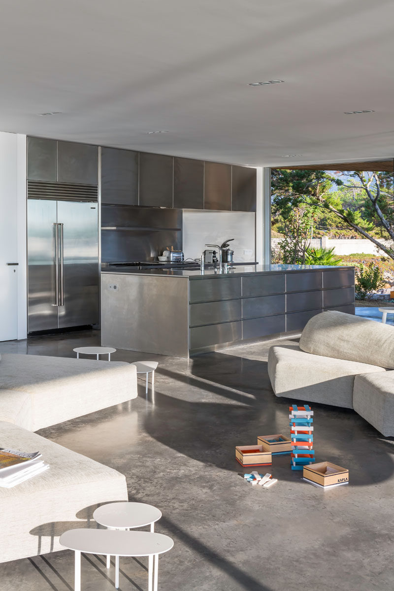 Sharing the open floor plan of the living and dining room in this modern villa is the kitchen. Concrete flooring and stainless steel cabinetry has been used to create more of an industrial looking space.