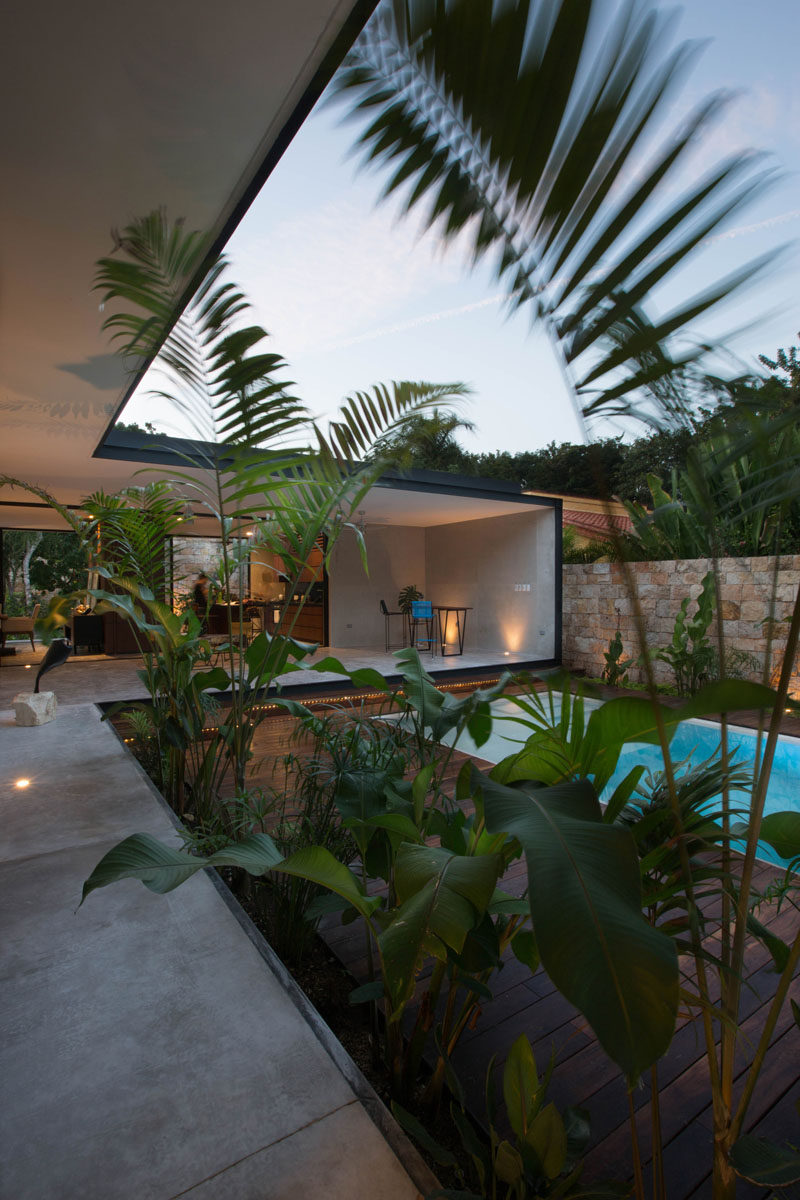 A small swimming pool in this courtyard is surrounded by a wood deck, and plants tie the space in with the natural feeling found throughout this home.