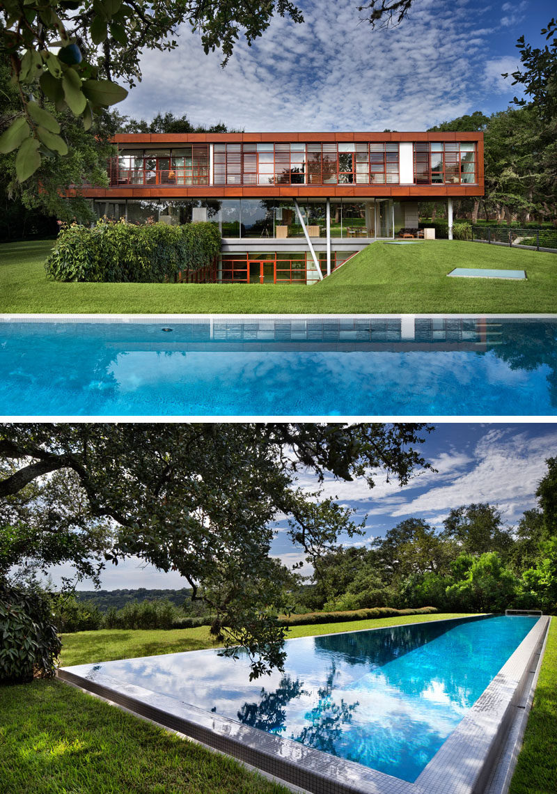 Skylights in the grass provide light to the rooms in the lower level of this modern home, and the large swimming pool is the perfect place to cool off.