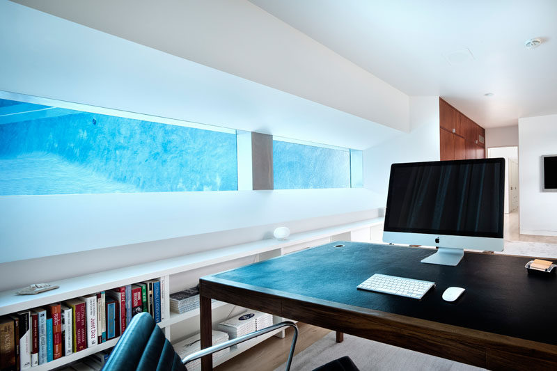 This home office is built into the ground and has a view of the pool from within the water.