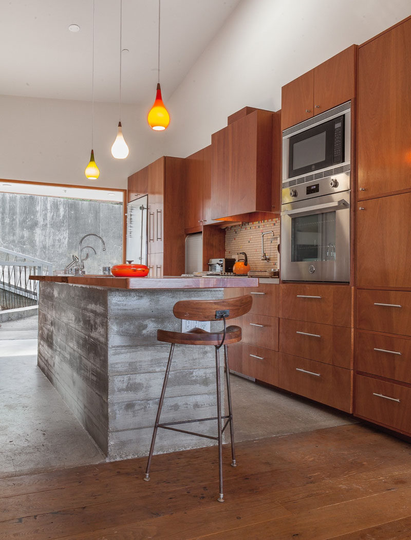 Raw concrete has been paired with wooden cabinetry and floors in this contemporary kitchen.