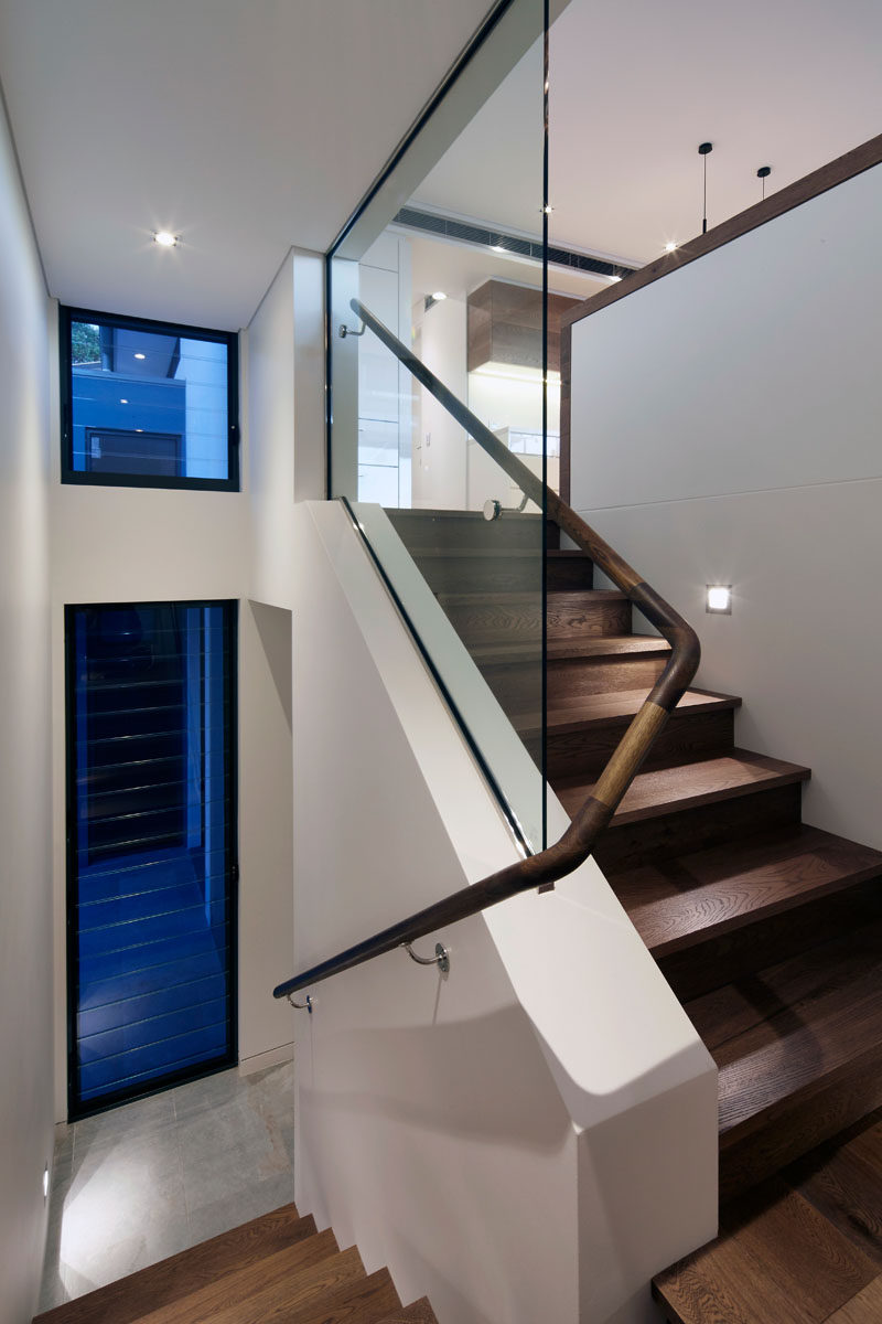 Inside this modern townhouse, white walls and wood feature throughout the interior, like in this staircase with a curved wooden handrail.