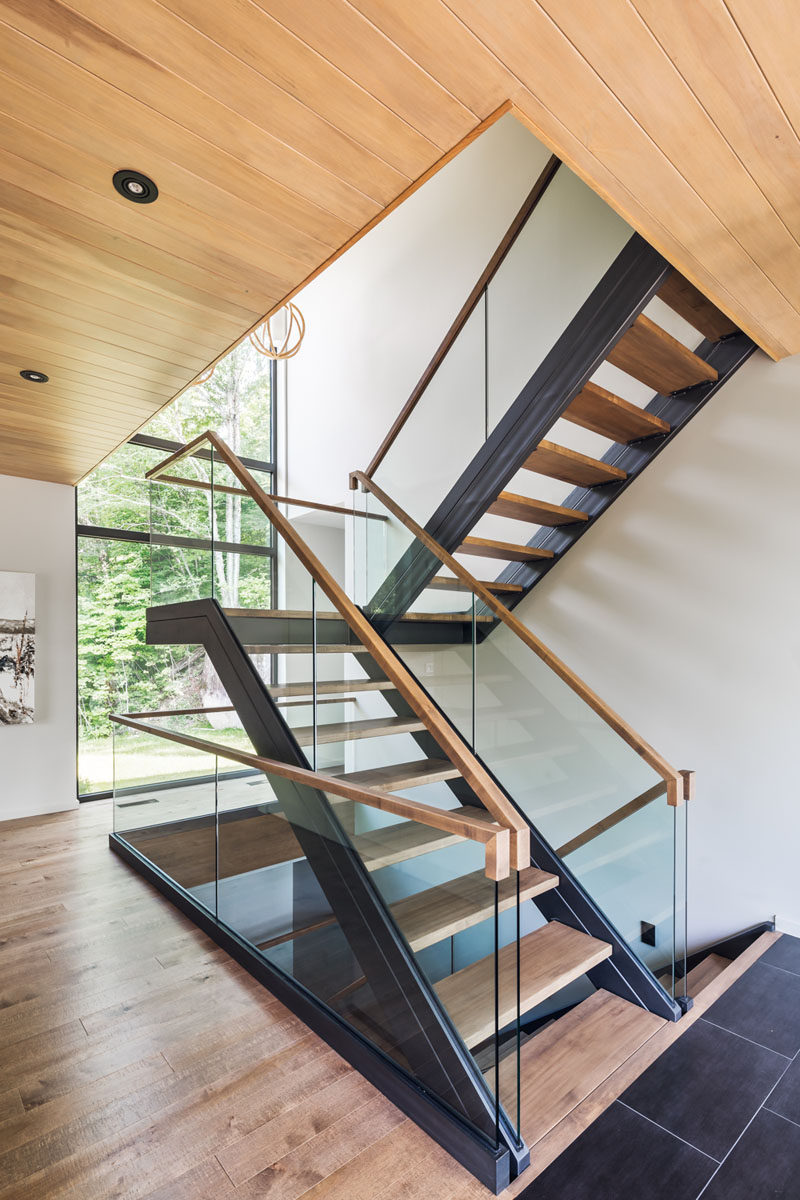 Stepping inside this contemporary home, you are greeted by a staircase that's filled with natural light from the large windows overlooking the backyard.