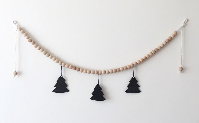 15 Decor Ideas For Creating A Woodland Nursery Design // If you're going for a Scandinavian woodland look, a wood bead garland with tree silhouettes is a must have.