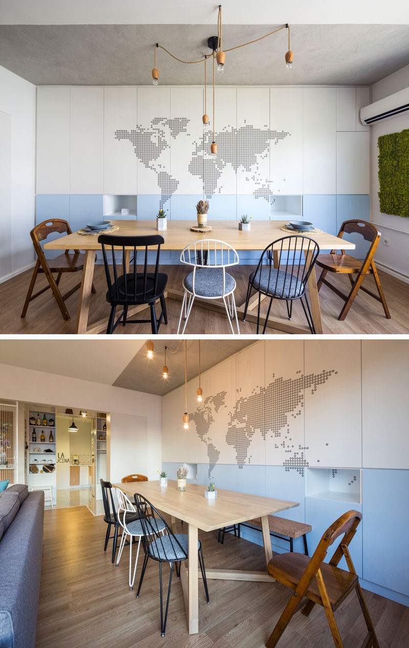 Behind this dining table, a wall of cabinets has a couple of small cut-outs that are used as shelves, and a map of the world has been added as an artistic feature.