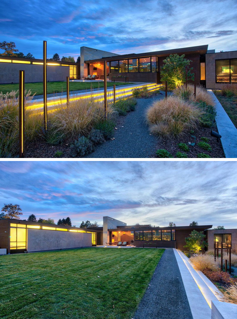 The backyard of this contemporary house has hidden lighting that highlights the steps that lead down to a landscaped area.