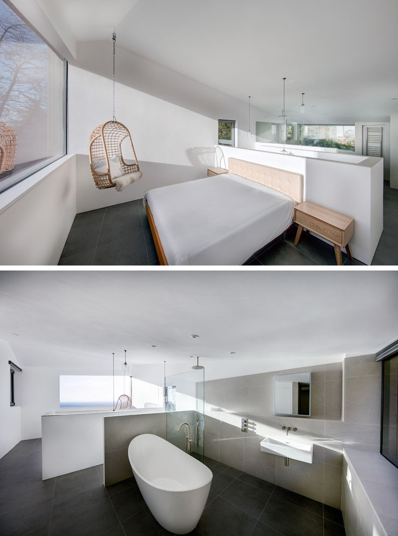This bedroom in a modern holiday home has a large window overlooking the water, and behind the bed an the open bathroom with a standalone tub, shower and vanity.
