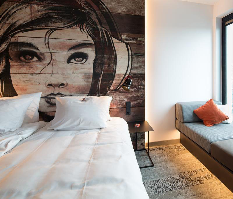 This bedroom has a mural painted on a headboard made from reclaimed wood