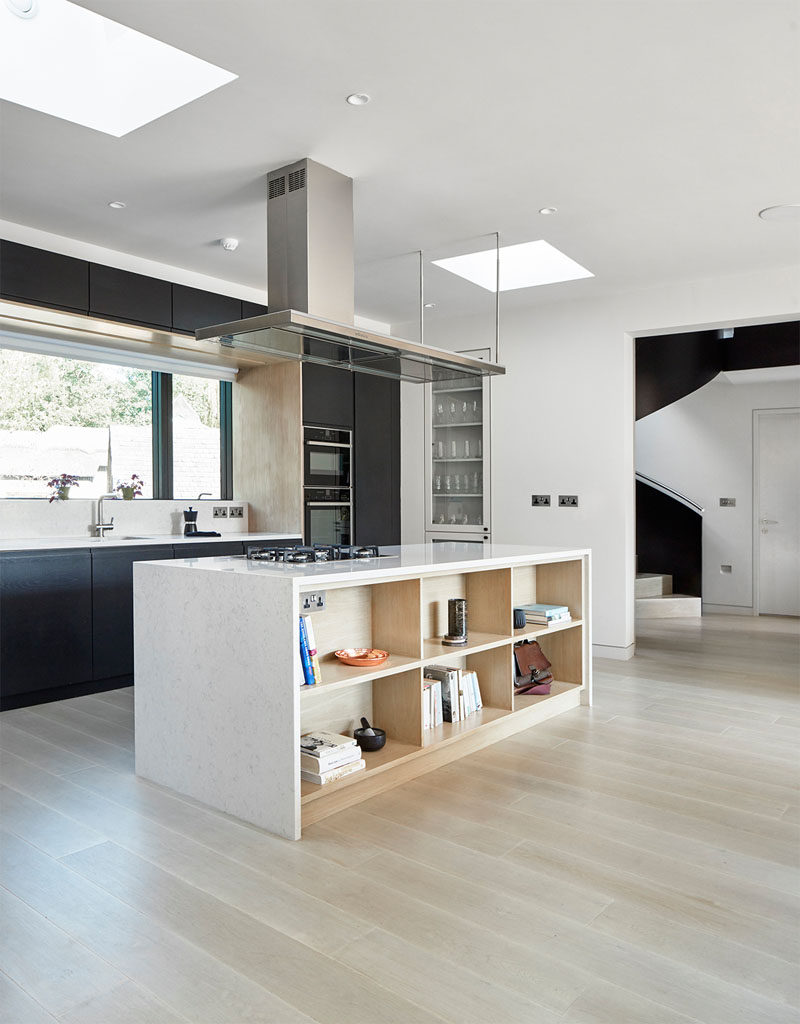 This modern kitchen has matte black cabinets and a large island with built-in open shelving.