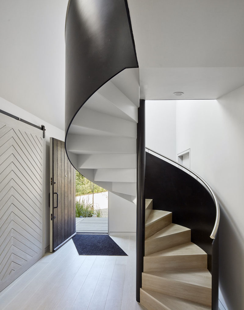 This modern entry hallway is home to a black, white and wood spiral staircase.