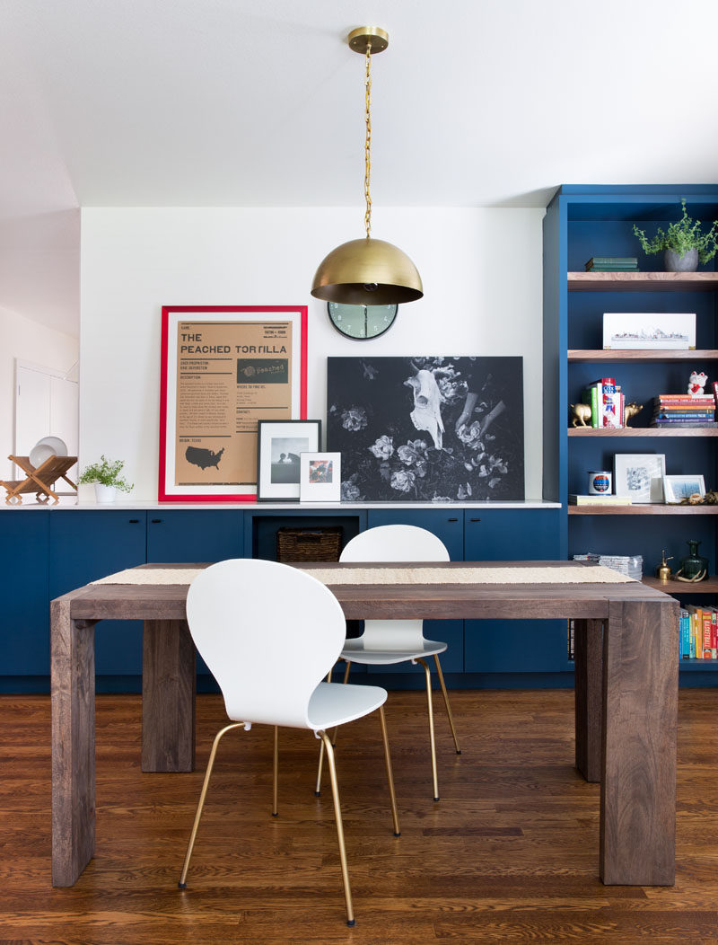 This Home In Austin Received An Updated White And Navy Blue Kitchen // The navy blue cabinetry, black hardware and brass accents create a simple yet sophisticated look in the kitchen while pops of color, like the red frame and colorful book on the shelf, bring in a touch of excitement and fun.