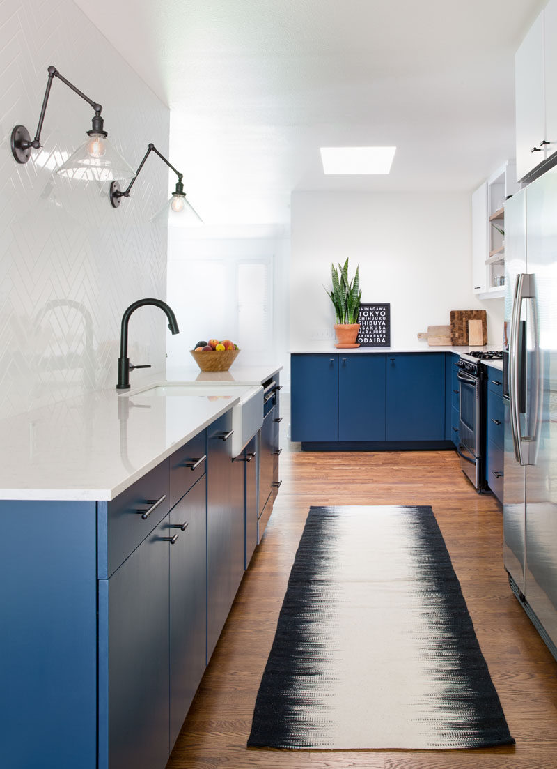 This Home In Austin Received An Updated White And Navy Blue Kitchen // Simple white tile arranged in a herringbone pattern covers the wall behind the sink and makes up the backsplash around the rest of the kitchen. It creates a contrast against the dark hardware and navy cabinets to make the space look clean and contemporary.