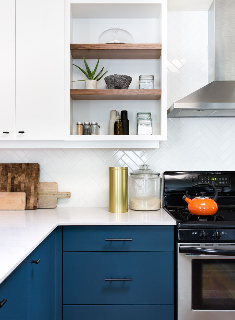 This Home In Austin Received An Updated White And Navy Blue Kitchen // A combination of open and closed shelving give the home owners freedom to display certain objects and keep the most frequently used herbs and spices easily accessible while hiding everything else out of sight.