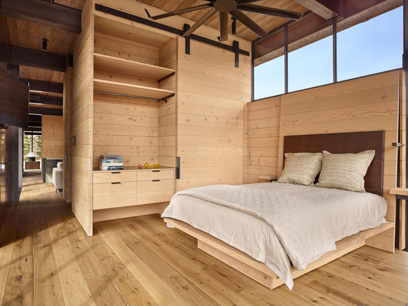 This bedroom has a warm and cozy feel to it with the use of wood, however industrial elements like the fan and sliding barn door are also included.