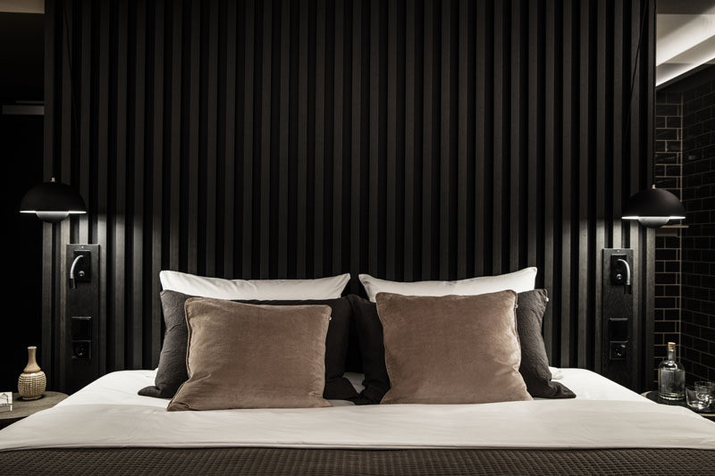 To create a dramatic and dark modern bedroom design, install a black accent wall or headboard like this one, made from black wooden slats. #DarkBedroom #BlackHeadboard #ModernBedroom #BedroomDesign