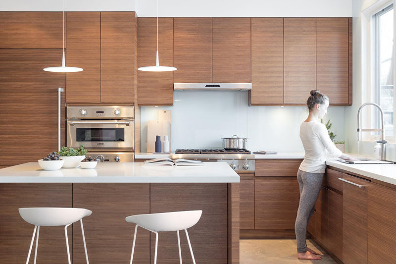 Walnut kitchen cabinets and white quartz countertops with a glass backsplash make up the color palette in this modern kitchen.