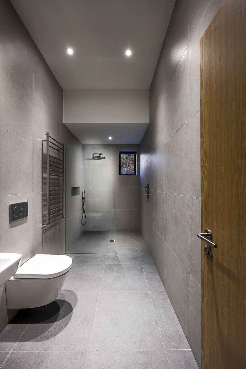 This modern bathroom features large grey tiles covering both the floor and walls.