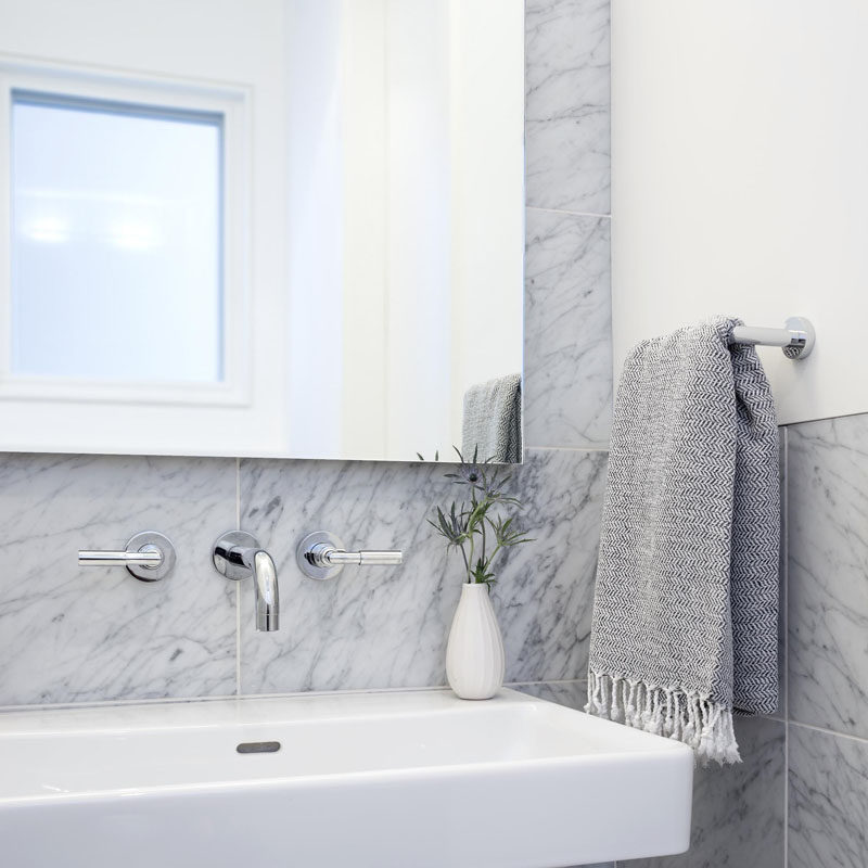 A simple palette of white Carrara marble with a white vanity has been used in this modern bathroom.