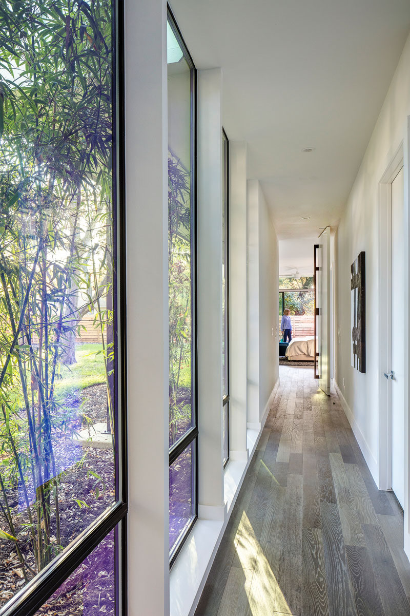 This modern hallway with floor-to-ceiling windows connects the master bedroom with the rest of the house.
