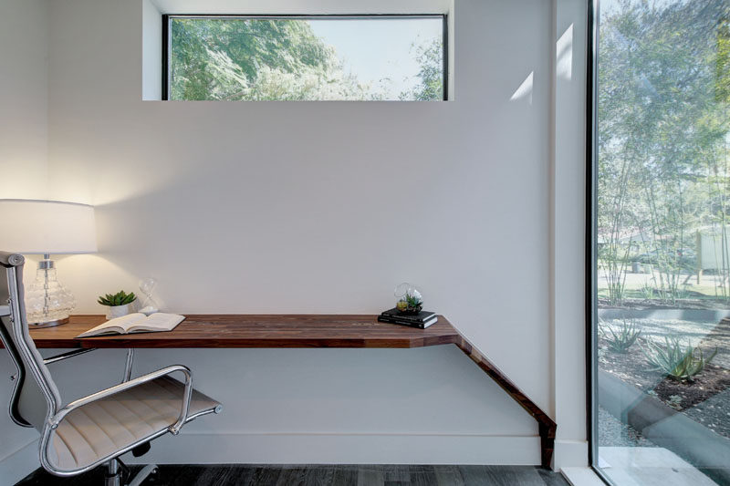 This small home office with a built-in wood desk has views of the garden through a large floor-to-ceiling window.