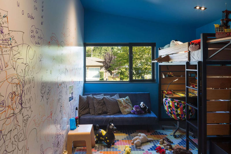 A dry erase wall, bold blue walls and a raised bed with a desk underneath make this kids room fun and playful.